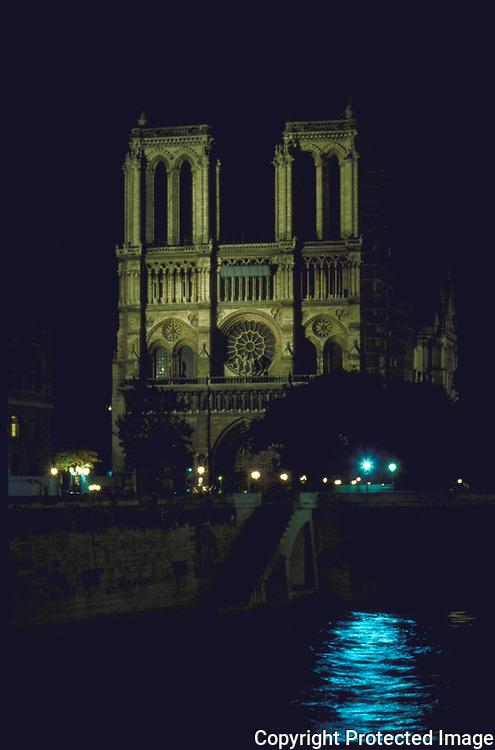 Notre Dame of Paris by night, the Seine is shown alongside the church on the Ile De Le Cite