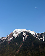 Mount Cheam in the early spring with the moon rising above it.  Photographed in Agassiz, British Columbia, Canada.