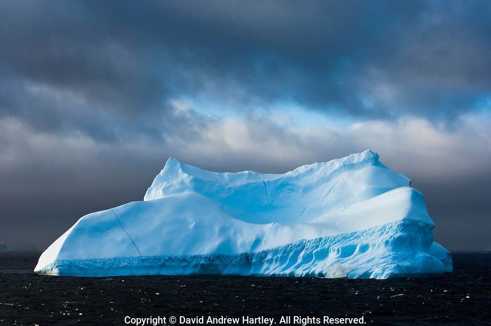 Grey storm clouds pass over an iceberg,.South Orkney Islands, Scotia Sea, South Atlantic Ocean