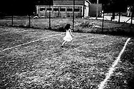 A kid runs out the football field of the center. FEDASIL Sugny asylum center. Sugny, Belgium. July 2015. I took these photographs during an international volunteer program that I liderate with an international volunteering group.