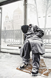 A homeless sleeps at the bus stop near the Christ the Savior Cathedral (in the background) during the heavy snowfall in Moscow Friday 28 January 2005. Up to 20 centimeters of snow falled during past 24 hours in Moscow.