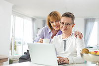 Loving couple using laptop together at home