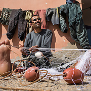 Après la sortie en mer du matin, les pêcheurs s'attèlent à réparer leur filet ou entretenir leur matériel.