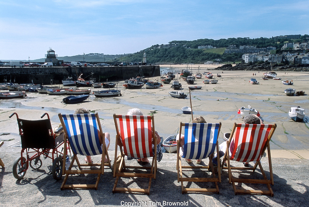 sunning themselves in the summer sun on the sea wall at St. Ives., England