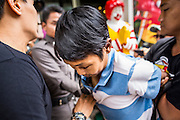 """31 MAY 2014 - BANGKOK, THAILAND: A young man is led away by Royal Thai Police after he walked down a sidewalk holding a sign that said """"Respect my vote"""" in a solitary protest against the military government. Bangkok was mostly quiet Saturday. There were only a few isolated protests against the coup and military government.    PHOTO BY JACK KURTZ"""