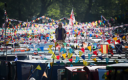© Licensed to London News Pictures. 06/05/2018. London, UK. A boat owner stands amongst colourful bunting at day two of the Canalway Cavalcade festival takes place in Little Venice, West London on Sunday,  May 6th 2018. Inland Waterways Association's annual gathering of canal boats brings around 130 decorated boats together in Little Venice's canals on May bank holiday weekend. Photo credit: Ben Cawthra/LNP