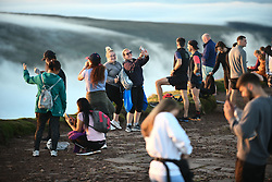 © Licensed to London News Pictures. 08/08/2020. City, UK. Walkers take selfies during the morning sunrise from the summit of Pen-y-Fan in the Brecon Beacons, on what is expected to be the hottest day of the year across the UK. The mountain which is the highest in southern Britain, has become increasingly popular with visitors who reach the top of the peak at first light to see the sun rising from the horizon. Photo credit: Robert Melen/LNP