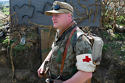 A reenactor portraying a German paratrooper medical office (Fallschirmjäger, Sanitätsunteroffizier) wearing Red Cross Armband, Splinter Pattern Jump Smock and Tropical Cap at he Yorkshire War Experience <br />