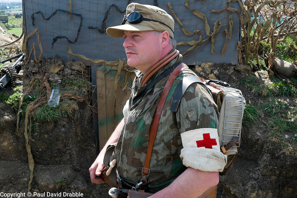 A reenactor portraying a German paratrooper medical office (Fallschirmj&auml;ger, Sanit&auml;tsunteroffizier) wearing Red Cross Armband, Splinter Pattern Jump Smock and Tropical Cap at he Yorkshire War Experience <br />
