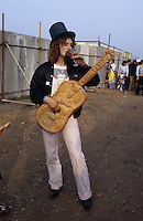 Scottish singer and comedian Billy Connolly, with a guitar apparently made of bread, at an outdoor festival, circa 1975.