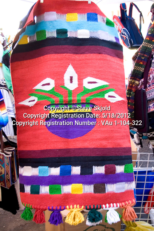 Colorful tapestry hanging for sale in a sidewalk festival shop. Mexican Independence Day Minneapolis Minnesota MN USA