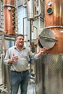 Standing beside a custom built copper still, proprietor Scott Maitland discusses his Topo Distillery, Chapel Hill, organic spirits and wheat beer.