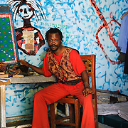 "Psychiatric patient, Samuel, believes he is Emperor Haile Selassie I of Ethiopia. He painted the walls of his room himself, and says the figure on the wall next to him is his ""spiritual interlocutor"". He says he was inspired to paint the guitar after he saw God, who was walking towards him ""playing a guitar in a rasta style."" Local lore has it that he fell ill after marrying a girlfriend in the underworld."