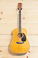 Martin guitar hanged against wood grain wall