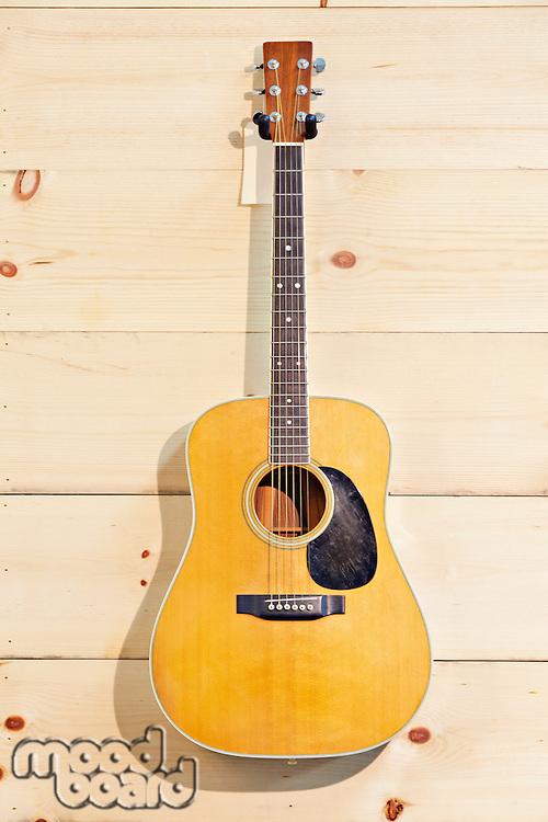 Martin guitar hanged against wood grain wall