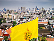 """27 NOVEMBER 2012 - BANGKOK, THAILAND: The flag of the Thai monarchy flies over the city of Bangkok from the top of Wat Saket during the annual temple fair. Wat Saket, popularly known as the Golden Mount or """"Phu Khao Thong,"""" is one of the most popular and oldest Buddhist temples in Bangkok. It dates to the Ayutthaya period (roughly 1350-1767 AD) and was renovated extensively when the Siamese fled Ayutthaya and established their new capitol in Bangkok. The temple holds an annual fair in November, the week of the full moon. It's one of the most popular temple fairs in Bangkok. The fair draws people from across Bangkok and spills out in the streets around the temple.    PHOTO BY JACK KURTZ"""