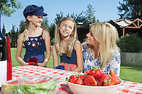 Mother communicating with daughters while sitting at outdoor dining table
