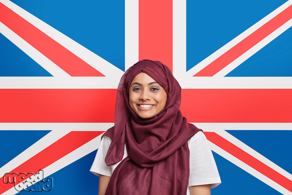 Portrait of happy young Muslim woman in traditional clothing standing against British flag