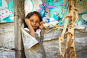 A girl living in La Chureca, Managua, Nicaragua's garbage dump barrio, peers at visitors from behind her home.