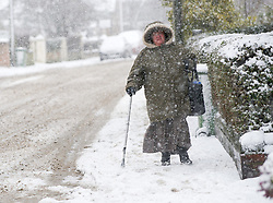 © Licensed to London News Pictures. 13/03/2013..North Yorkshire, England..A woman makes her way down the snow covered main street of Hinderwell as heavy snow falls over North Yorkshire as the wintery weather continues...Photo credit : Ian Forsyth/LNP