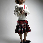 White Plains, NY / 2007 - Thrift store designer clothes for kids.  Model: Kate Evans, 7.  Cream top with brown stitching, Sally Mack, $9. Milk Money Red plaid skirt, The Children's Place, $10. Affordables; Mary Jane shoes, Mod 8, $10. Affordables; Black flower necklace $1. Milk Money; Pink necklaces 3 for $1. Milk Money; Book, American Girls Collection, $2. Affordables Denim purse, Abercrombie, $2.50. ( Mike Roy / The Journal News )