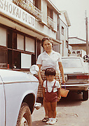 grandmother with grandchild posing outside Japan Yokosuka late 1960s