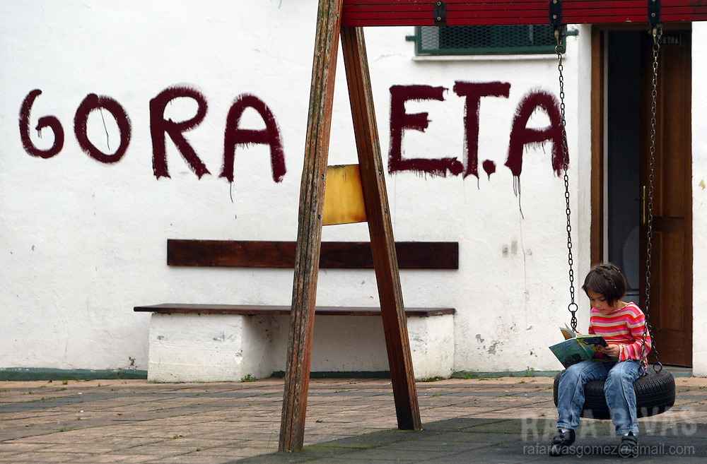 A girl reads a book next to graffiti supporting armed Basque separatist group ETA, 18 October 2007 in the northern Spanish Basque village of Lizartza. PHOTO RAFA RIVAS