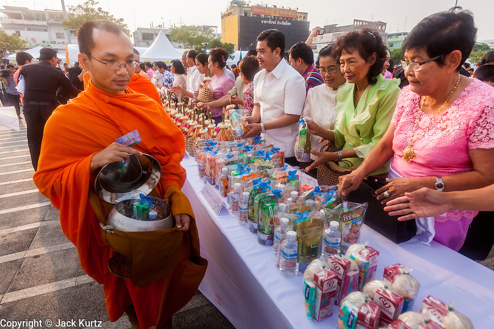 13 APRIL 2014 - BANGKOK, THAILAND: People give alms to monks during a merit making ceremony for Songkran at Bangkok City Hall. Many people go to temples and religious ceremonies to make merit on Songkran. Songkran is celebrated in Thailand as the traditional New Year's Day from 13 to 16 April. Songkran is in the hottest time of the year in Thailand, at the end of the dry season and provides an excuse for people to cool off in friendly water fights that take place throughout the country. Songkran has been a national holiday since 1940, when Thailand moved the first day of the year to January 1.    PHOTO BY JACK KURTZ