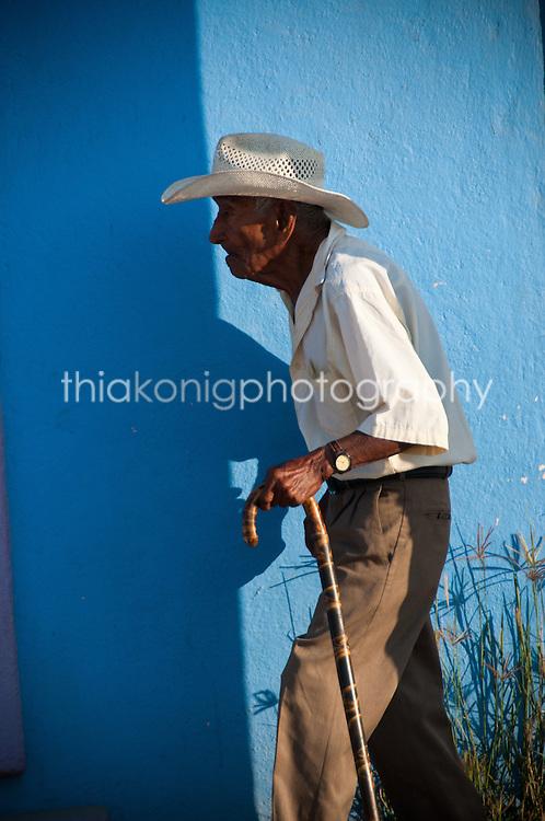 Old man walks in front of blue wall, Barra de Navidad, Mexico