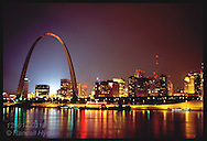 Night view of downtown St. Louis riverfront with Arch and riverboats. Missouri