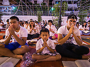31 DECEMBER 2013 - BANGKOK, THAILAND:   People pray at Wat Pathum Wanaram on New Year's Eve in Bangkok. Hundreds of thousands of people pack into the Ratchaprasong Intersection in Bangkok for the city's annual New Year's Eve countdown. Many Thais go the Erawan Shrine and Wat Pathum Wanaram near the intersection to pray and make merit.   PHOTO BY JACK KURTZ