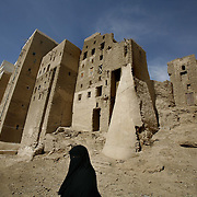 A woman walks past ancient buidings in Shibam. Shibam, a fortified 16th century city, is one of the oldest and best examples of urban planning based on the principle of vertical construction. The tower like buildings have been dubbed 'the Manhattan of the desert'.