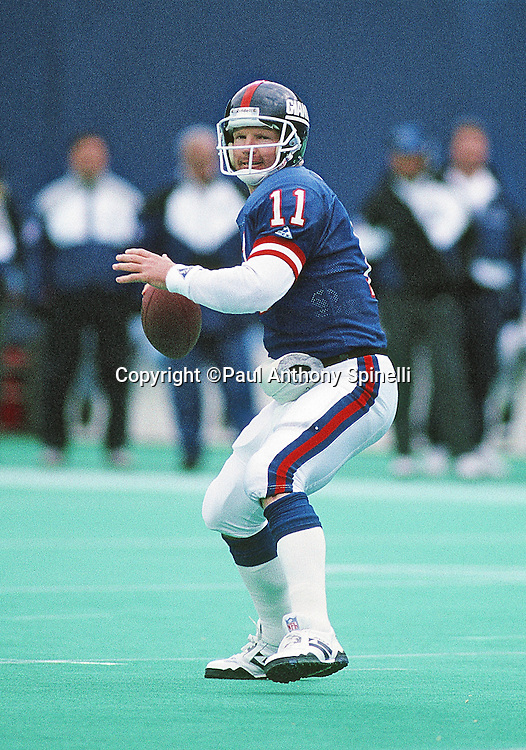 New York Giants quarterback Phil Simms (11) throws a pass during the NFL football game against the Dallas Cowboys on Jan. 2, 1994 in East Rutherford, N.J. The Cowboys won the game in overtime 16-13. (©Paul Anthony Spinelli)