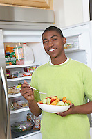 Young man eating salad by open fridge