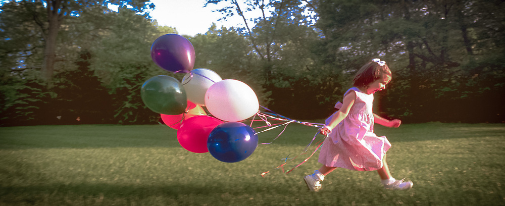 young girl runs trailing balloons