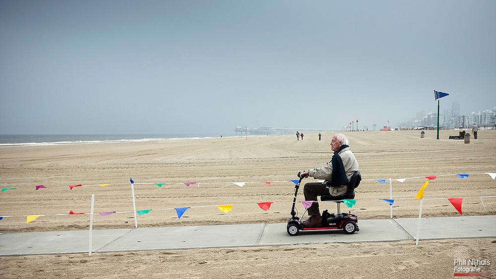 Scheveningen 30 mei 2013 - Een man op de een scootmobiel probeert het betonnen pad naar zee uit.<br /> Op het strand van Scheveningen is er een speciaal pad van beton naar de zee toe aangelegd voor scootmobielers en minder validen de mogelijkheid te geven om naar de zee en strand te kunnen gaan.