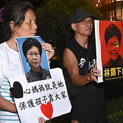 Two protesters exhibit their signs depicting the current Chief Executive of Hong Kong, Carrie Lam. Protests erupted this June in opposition to a controversial extradition bill.