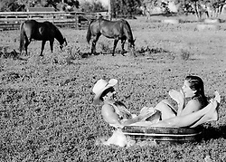 Couple enjoying being in a bath outdoors on a ranch with horses in the background