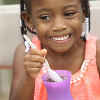 """Jahara Miller, 4, of Plantersville, fights off the freeze from her grape snow cone she bought at the """"Give Cancer the Boot"""" Relay for Life event at Parkway Elementary School Friday night in Tupelo. Lee County Relay for Life is an annual team fundraising event that benefits the American Cancer Society. This years theme was Give Cancer the Boot."""