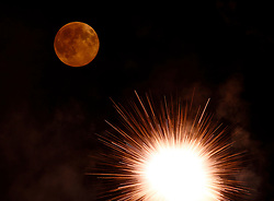 A fireworks petard explodes in front of the supermoon outside the town of Mosta, celebrating the feast of its patron saint, in central Malta, August 10, 2014. The astronomical event occurs when the moon is closest to the Earth in its orbit, making it appear much larger and brighter than usual.<br /> REUTERS/Darrin Zammit Lupi (MALTA)