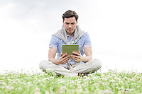 Full length of young man holding digital tablet while sitting on grass against sky