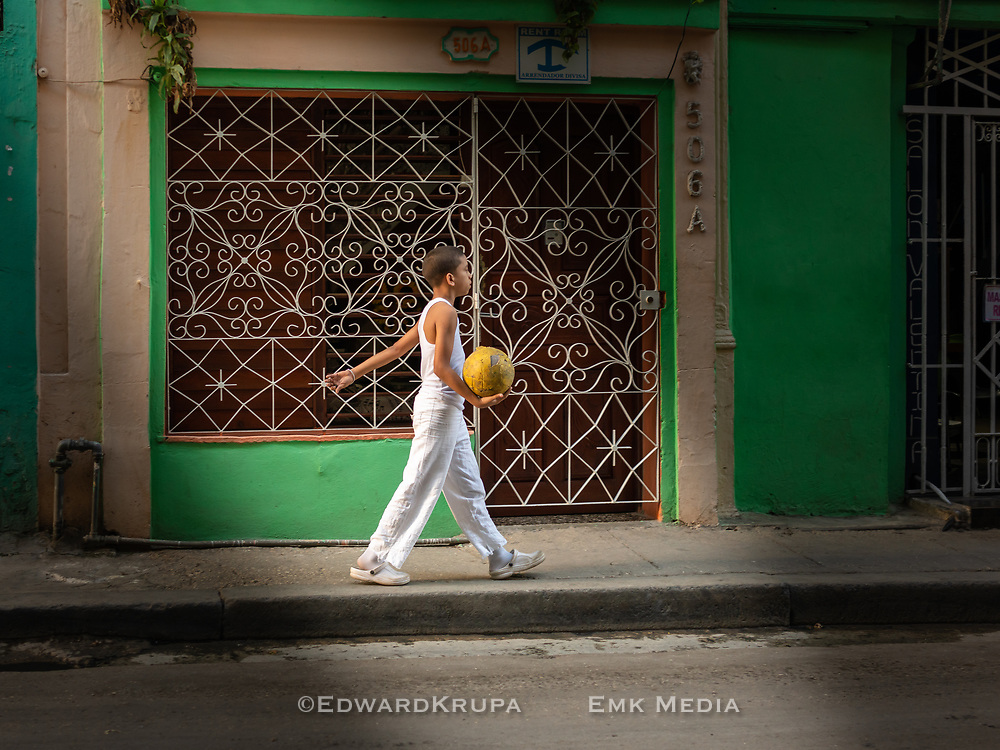 Boy in white clothes, walking with a yellow soccer ball in Havana.
