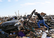 Jon Booth wrestles with debris from his mothers tornado-destroyed home across the street from the Plaza Towers elementary school in Moore, Oklahoma May 22, 2013. A massive tornado tore through a suburb of Oklahoma City, wiping out whole blocks and killing at least 24.   REUTERS/Rick Wilking (UNITED STATES)