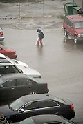 person wading through the water towards his car during a flood rain storm