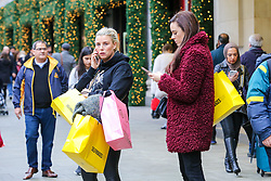 © Licensed to London News Pictures. 23/12/2018. London, UK. Women with shopping bags outside Selfridges store on Oxford Street. Last minute Christmas shoppers take advantage of pre-Christmas bargains in London's Oxford Street. Fewer shoppers have been reported shopping in Britain's high streets as online sales increase. Photo credit: Dinendra Haria/LNP