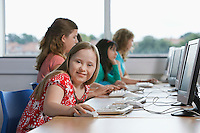 Portrait of girl (10-12) with Down syndrome in computer lab children in background