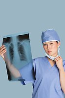 Portrait of a female surgeon holding x-ray report over light blue background