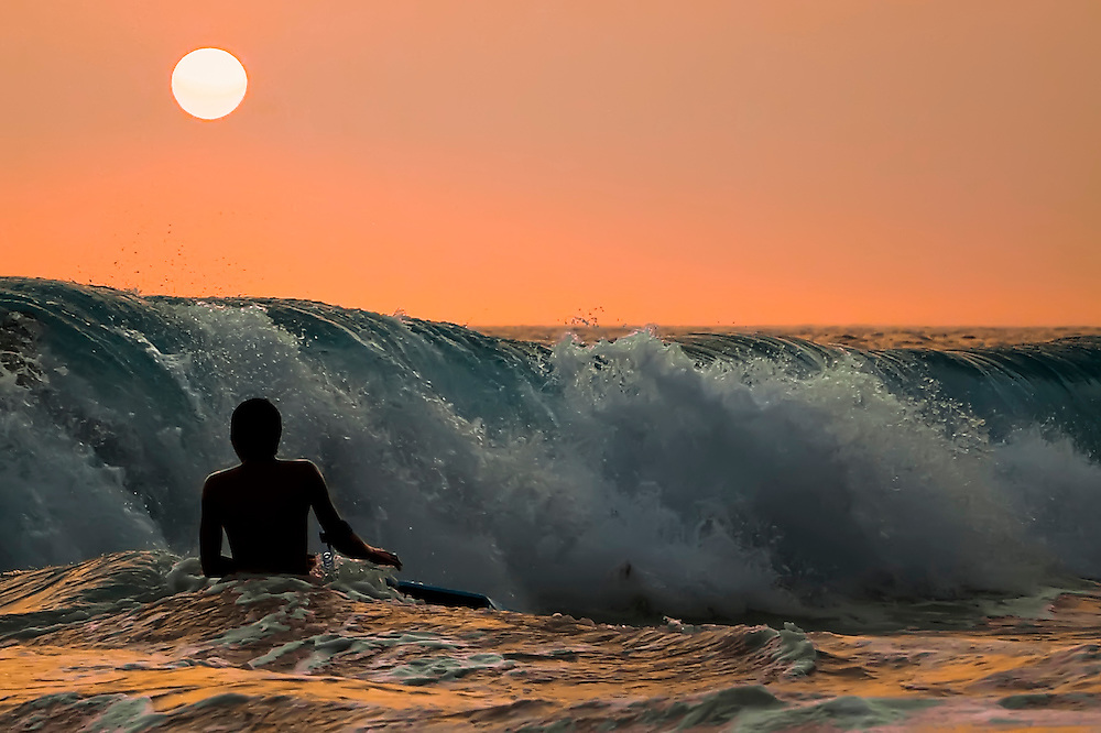 Lone boogie boarder enjoys big waves of late evening in Kona, HI.  Copyright 2009 Reid McNally.