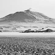 Looking across 20 miles of the Ross Ice Shelf at Ross Island, the summit of Mount Erebus volcano is 45 miles away. The dark area below Erebus is the Hut Point Peninsula where McMurdo Station is located at the end of the peninsula. Observation Hill can be made out on the right side of the peninsula, Arrival Heights on the left side, and Castle Rock is above and behind McMurdo. On the ice shelf below Hut Point you can see Pegasus Airfield, and several active science project locations.