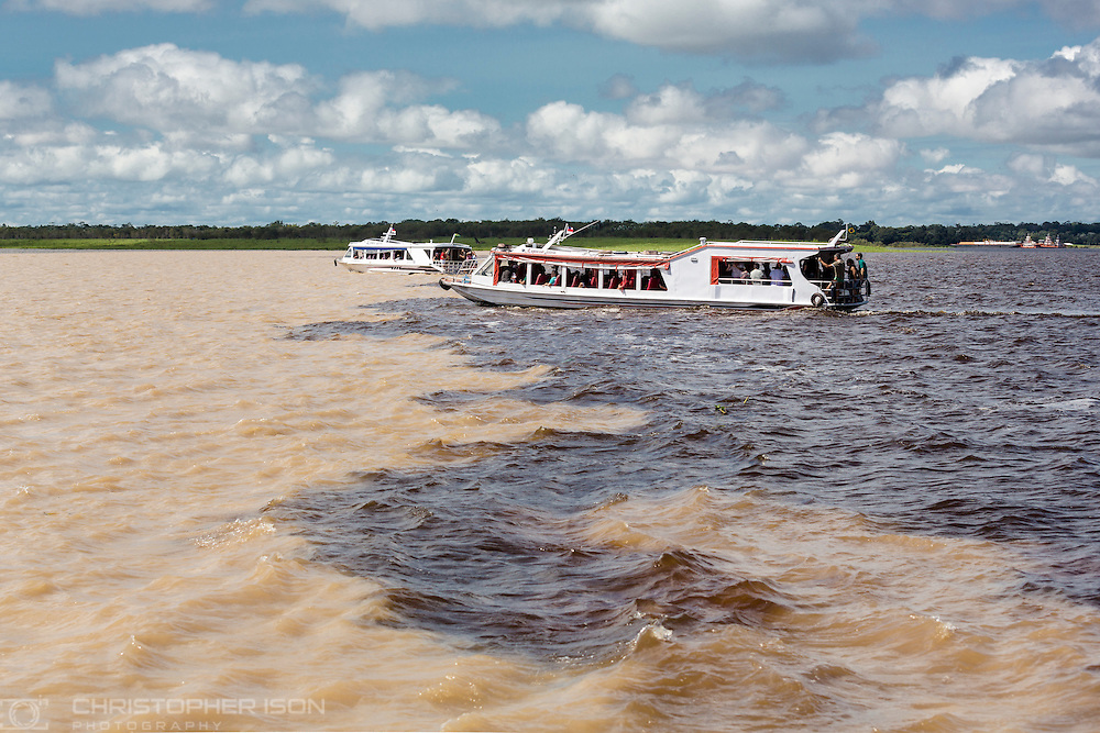 Tourist boats at the Meeting of the Waters on the Amazon River at Manaus in Brazil. The Rio Solimoes is lighter in colour because it flows more quickly and is also several degrees cooler than the Rio Negro to the right. Together, they form the mighty Amazon river.<br /> Picture date: Tuesday January 24, 2017.<br /> Photograph by Christopher Ison &copy;<br /> 07544044177<br /> chris@christopherison.com<br /> www.christopherison.com